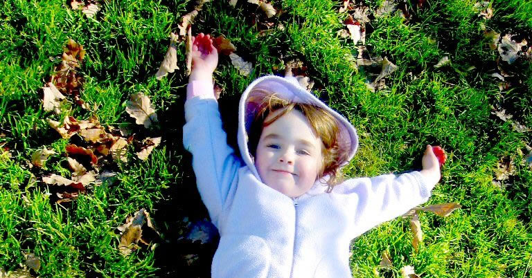 Little Girl Laying on Grass